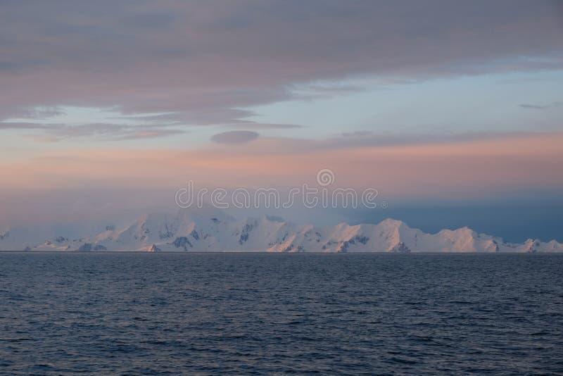 De kalme roze en blauwe zonsondergang van Antarctica over sneeuw afgedekte bergen stock foto