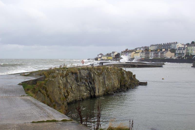 De kalme wateren binnen het beschutte Lange Gat herbergen neer in de Provincie van Bangor terwijl een onweer in het Ierse Overzee stock foto