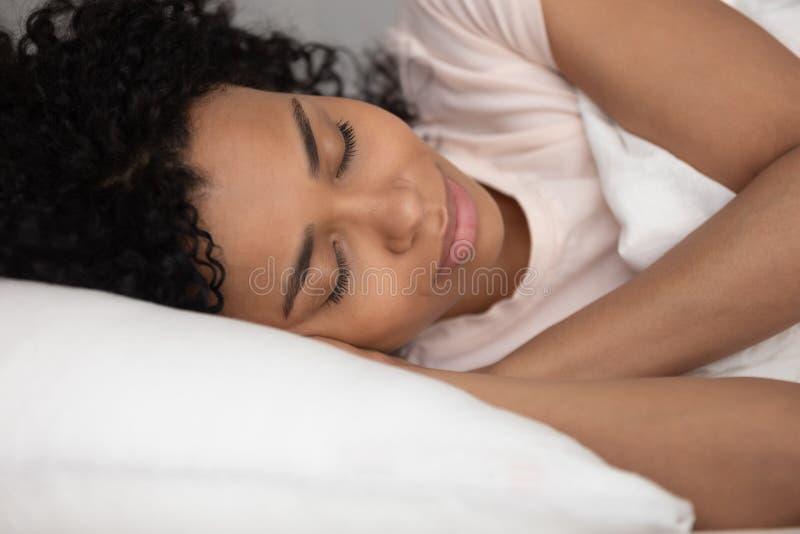 De kalme zwarteslaap goed in comfortabel bed, sluit omhoog stock foto