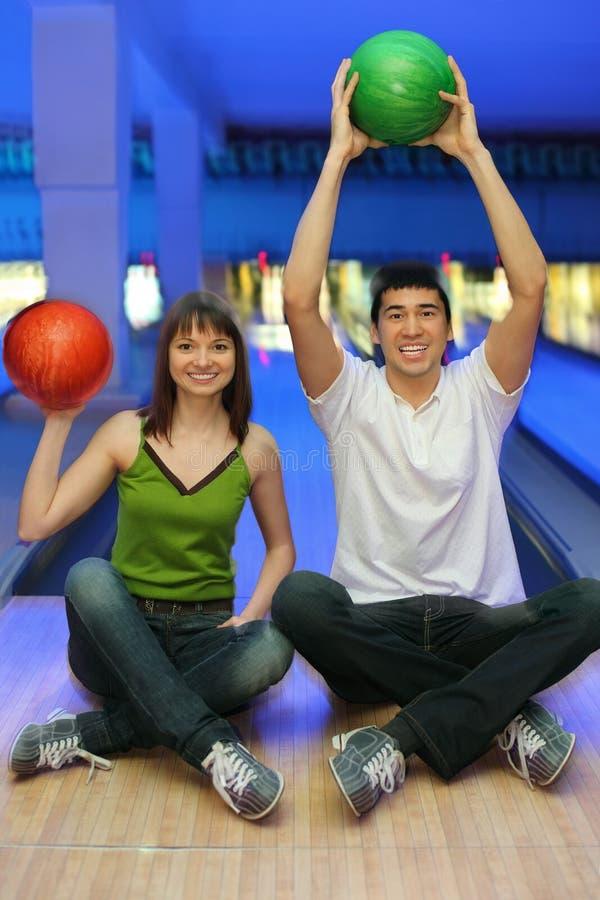 De kameraad en het meisje zitten en heffen upwards ballen op royalty-vrije stock afbeeldingen