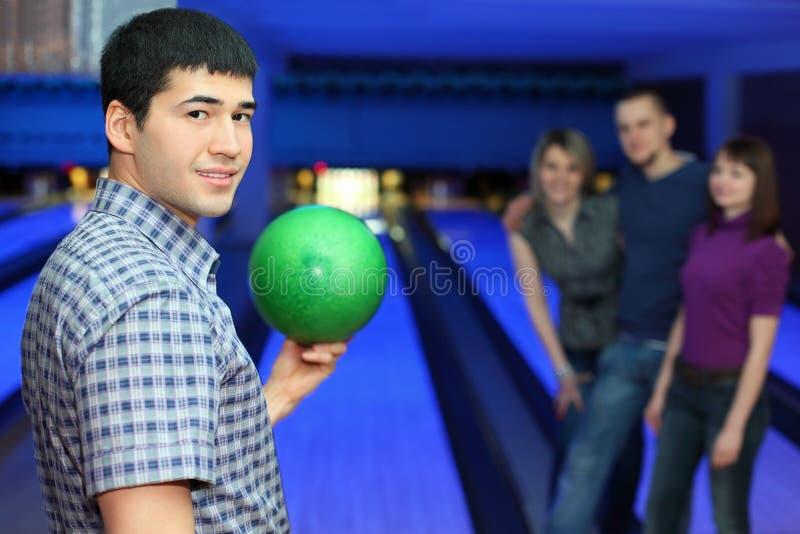 De kameraad houdt de bal voor kegelenvrienden hem bemoedigt stock foto's