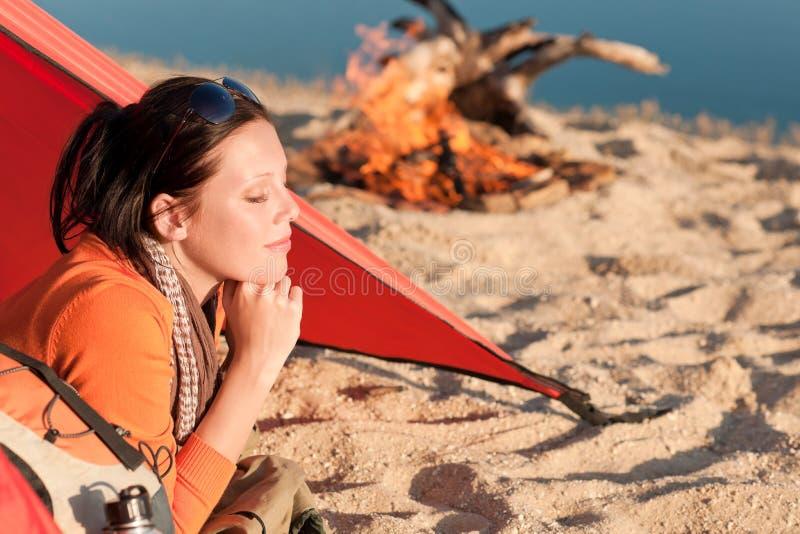 De kamperende gelukkige vrouw ontspant in tent door kampvuur stock afbeelding