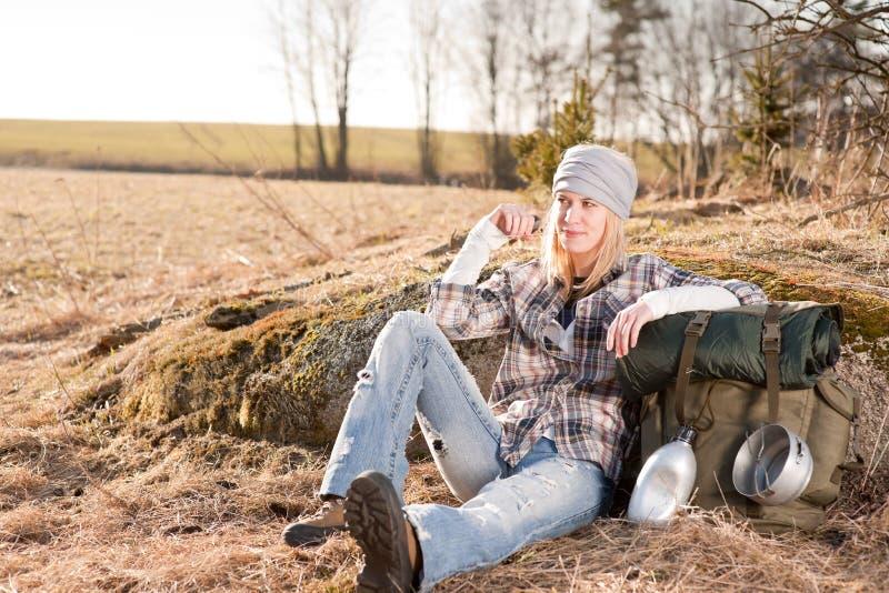 De kamperende jonge vrouw in plattelandsrugzak ontspant stock foto