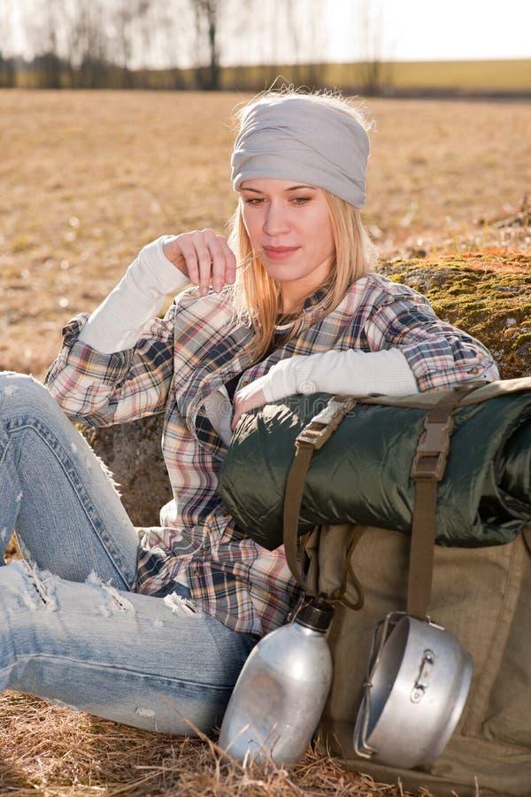 De kamperende jonge vrouw in plattelandsrugzak ontspant royalty-vrije stock fotografie
