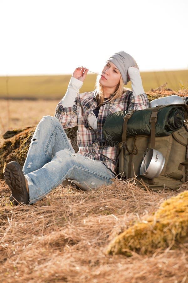 De kamperende jonge vrouw in plattelandsrugzak ontspant stock fotografie