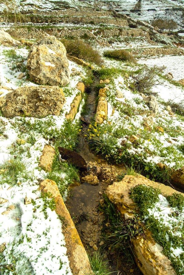 De kanalen van de landbouwers` s irrigatie op de hellingen van Qurnat als hoogste piek van Sawda - van Libanon ` s royalty-vrije stock foto