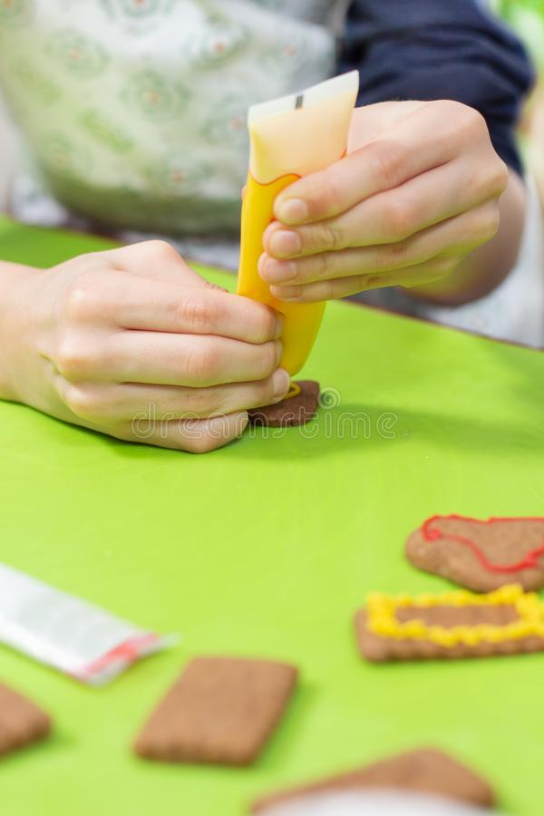 De kaneelkoekjes liggen op de groene lijst De handen van het kind drukken het gele berijpen uit de buis en leiden tot decoratie royalty-vrije stock afbeelding