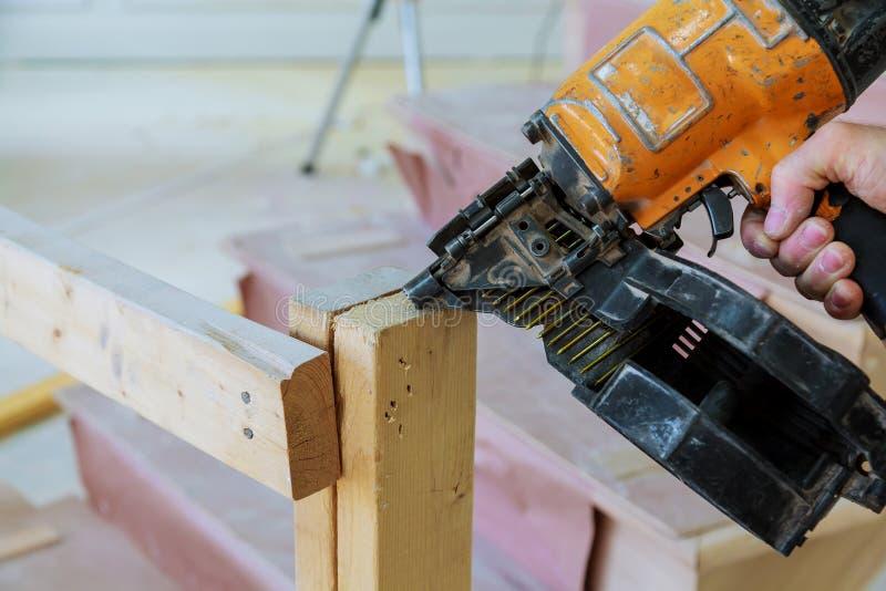 De kanonbouw schiet de spijkers de houten muur royalty-vrije stock afbeelding