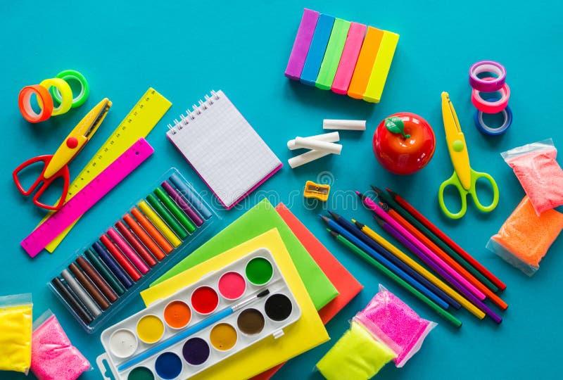 De kantoorbehoeften voor studie op school ligt op blauw Terug naar School Geluk en vredessymbool royalty-vrije stock afbeelding