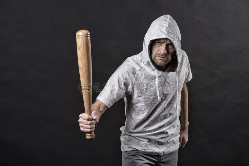 De kap van de hooliganslijtage in hoody, manier Het honkbalknuppel van de mensengreep, agressie De gangsterkerel dreigt met knupp royalty-vrije stock fotografie