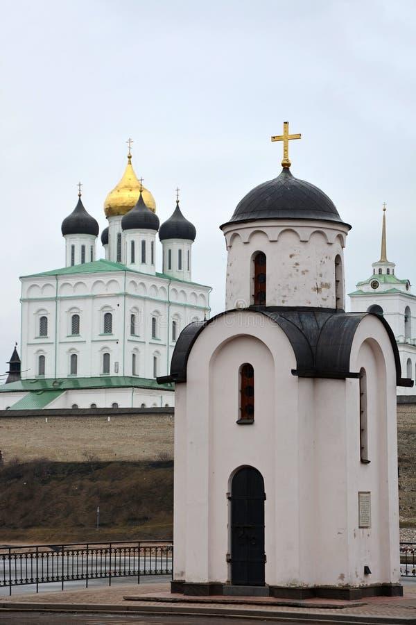 De kapel van Olga in Pskov, Rusland met Drievuldigheidskathedraal stock afbeelding