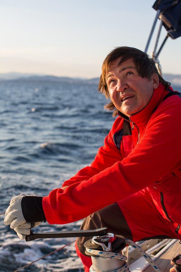 De kapitein bij de roercontroles van een varend jacht tijdens overzeese boten rent Sport stock foto's