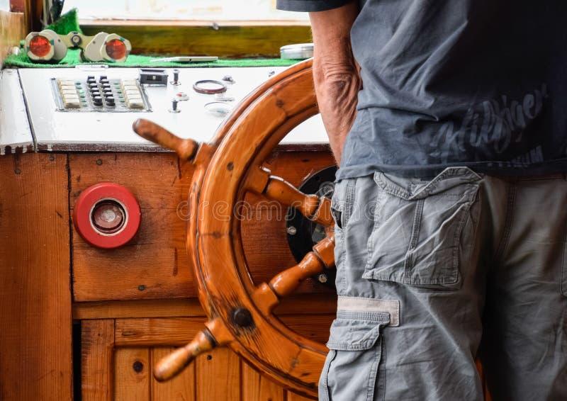 De kapitein van het schip bij het roer stock foto's