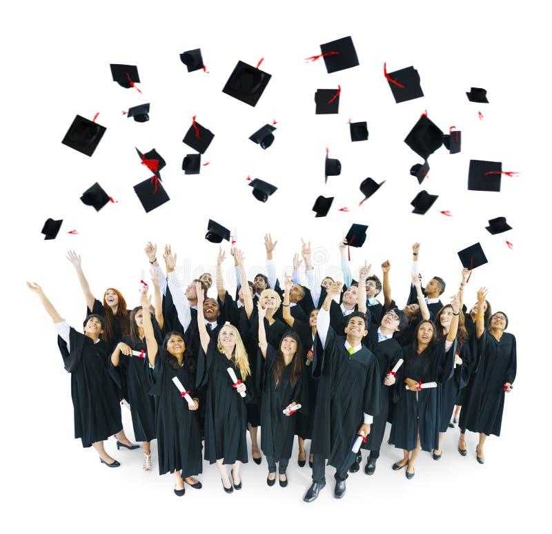 De Kappen van de graduatie die in de Lucht worden geworpen royalty-vrije stock afbeelding
