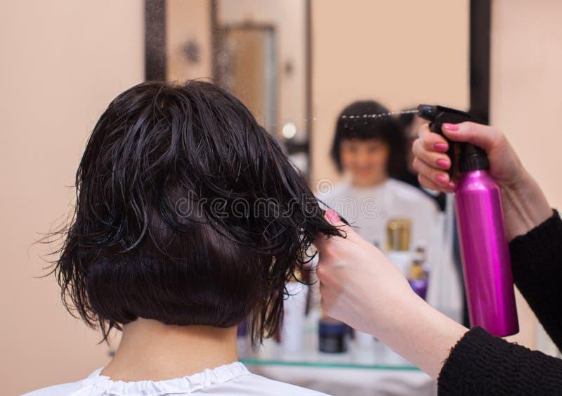De kapper alvorens zijn haar te drogen bestrooit een nevel op het donkerbruine haar van ` s royalty-vrije stock foto's
