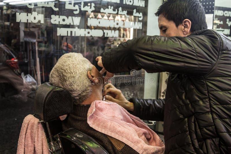 De kapper die één van zijn cliënt scheren bij nacht, in oud fashionned kapperswinkel aan de Europese kant van de stad royalty-vrije stock fotografie