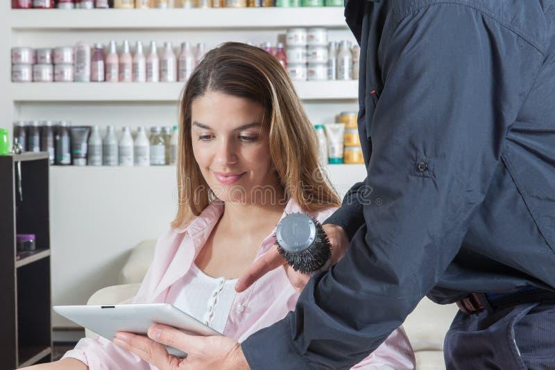 De kapper die aan één vrouw ipad tonen stock afbeeldingen