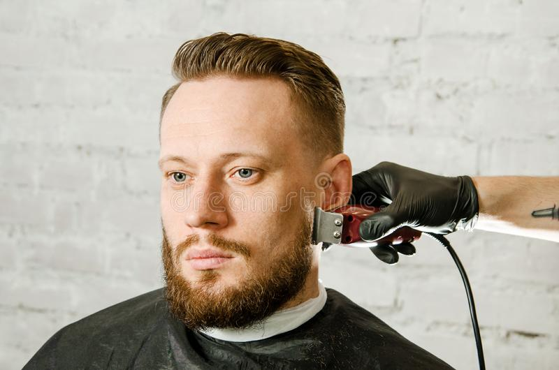 De kapper dient het haar van de handschoenenbesnoeiing en van scheerbeurten de volwassen gihger gebaarde mens op een bakstenen mu royalty-vrije stock afbeeldingen