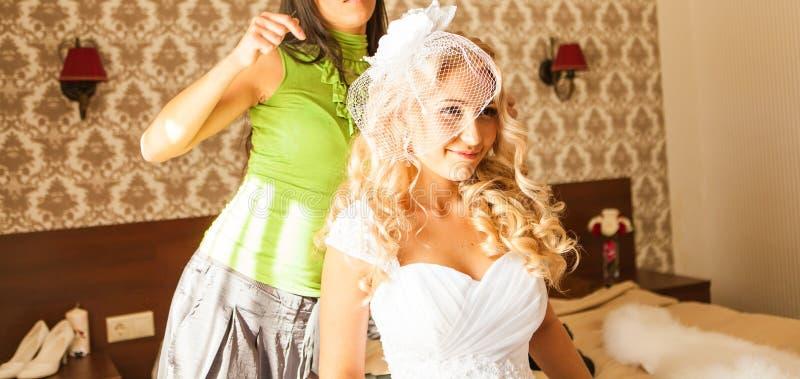 De kapper doet een kapsel aan de bruid stock afbeeldingen