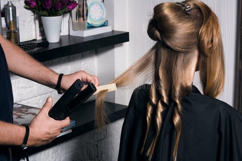 De kapper doet een kapsel aan een jonge vrouw royalty-vrije stock afbeeldingen
