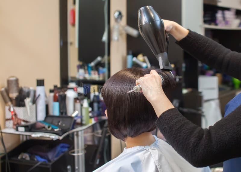 De kapper droogt haar haar een meisje in een schoonheidssalon stock afbeeldingen