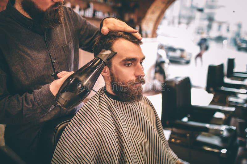 De kapper droogt het klanten` s haar met een tairdroger De klant kijkt neer royalty-vrije stock foto