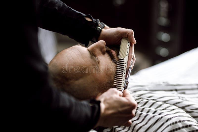 De kapper gekleed in een zwarte kleedt schaarbaard van de brutale mens in de modieuze herenkapper stock afbeeldingen