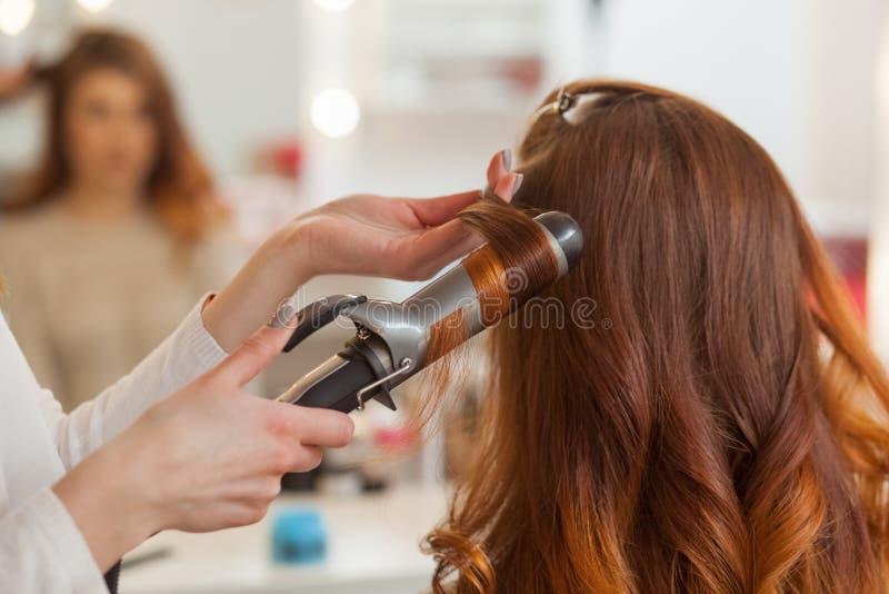 De kapper maakt kapselmeisje met lang rood haar in een schoonheidssalon Creeer krullen met het krullen van ijzers stock afbeeldingen