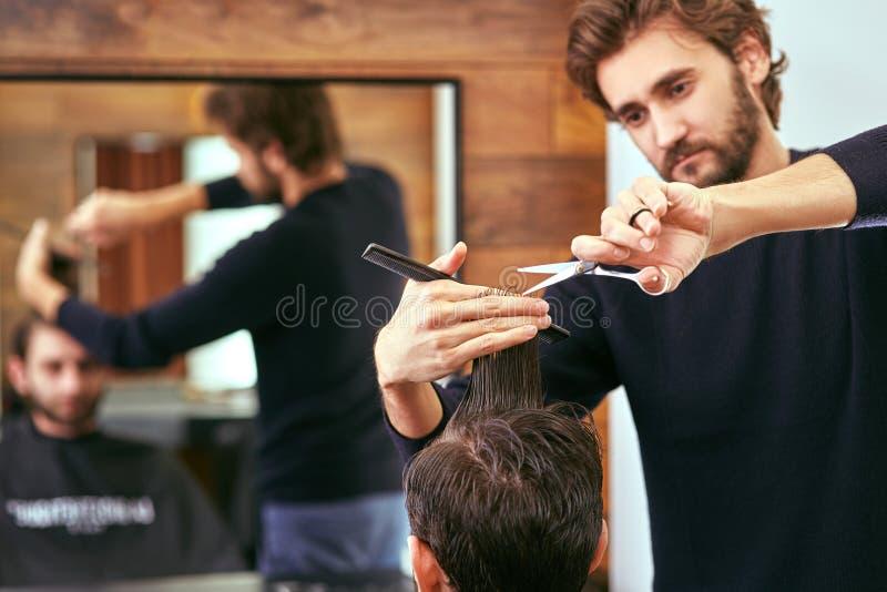 De kapper maakt mensenkapsel bij de schoonheidssalon royalty-vrije stock afbeeldingen