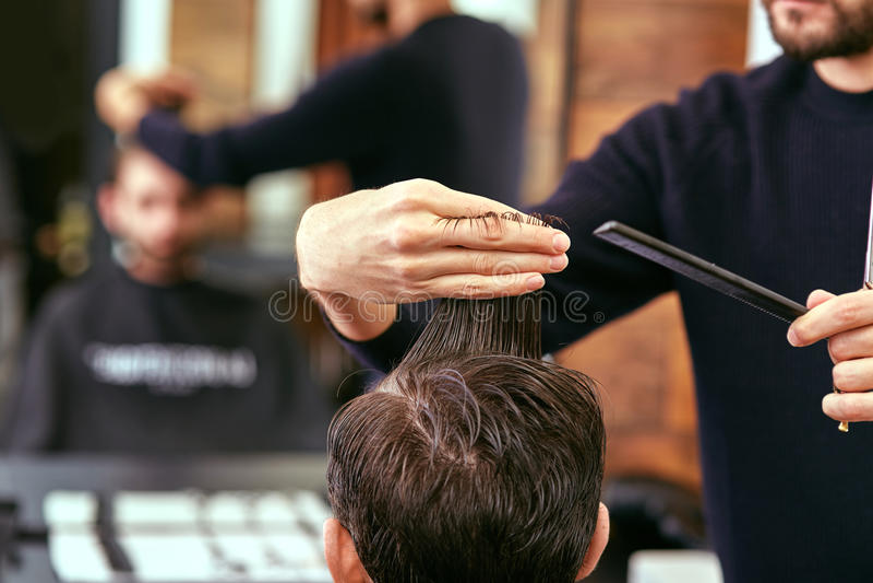 De kapper maakt mensenkapsel bij de schoonheidssalon stock afbeeldingen