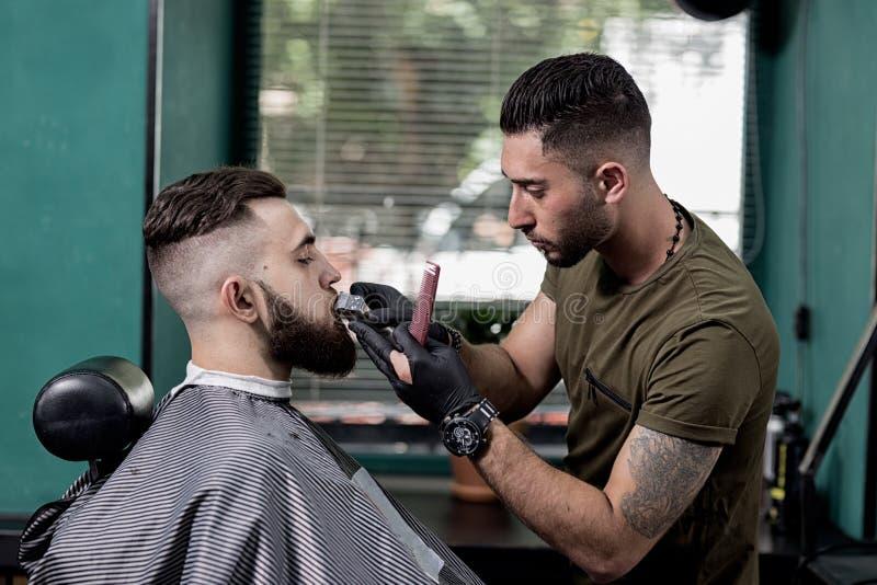 De kapper maakt snor van de donker-haired modieuze mens bij een herenkapper in orde royalty-vrije stock foto