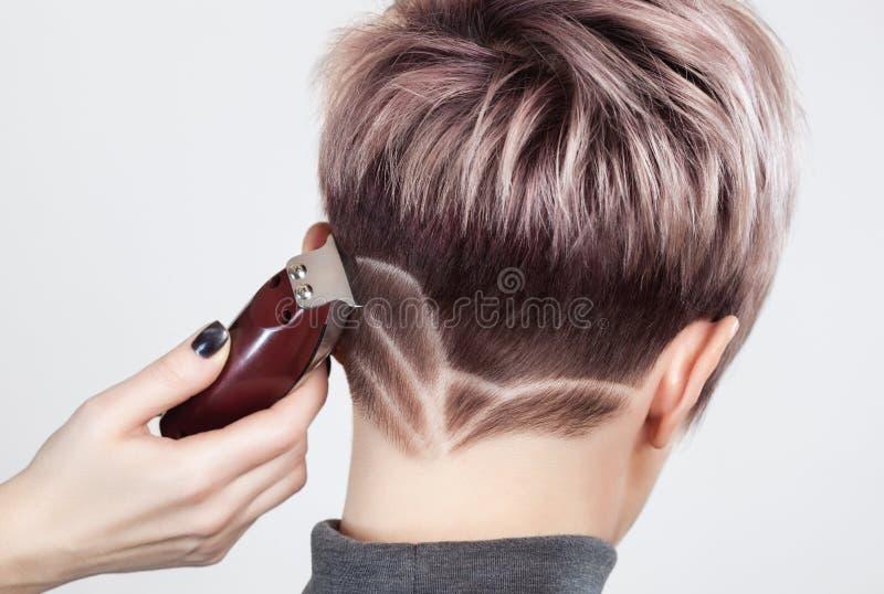 De kapper maakt tot een creatief kapsel met een scheermes aan een mooie vrouw stock afbeelding