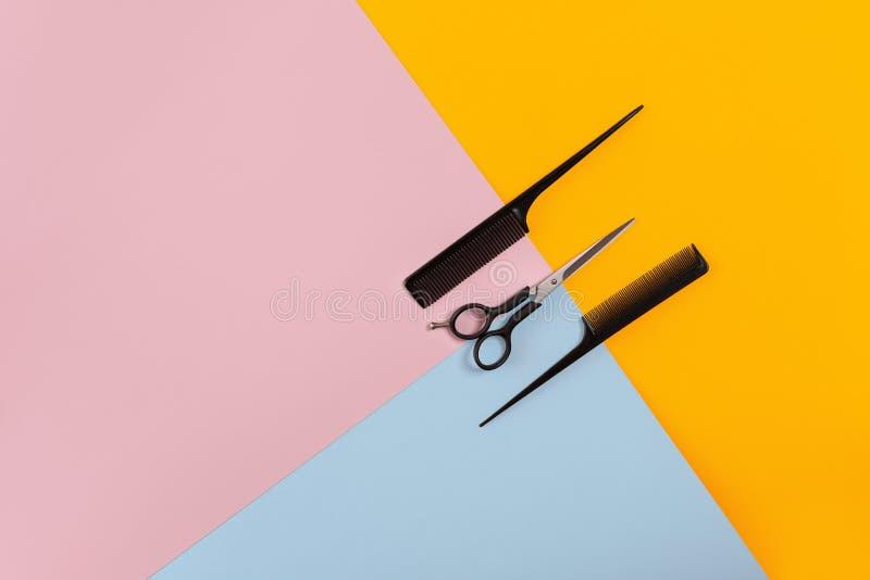 De kapper plaatste met twee kammen en schaar op de kleuren roze, gele, blauwe document achtergrond royalty-vrije stock fotografie