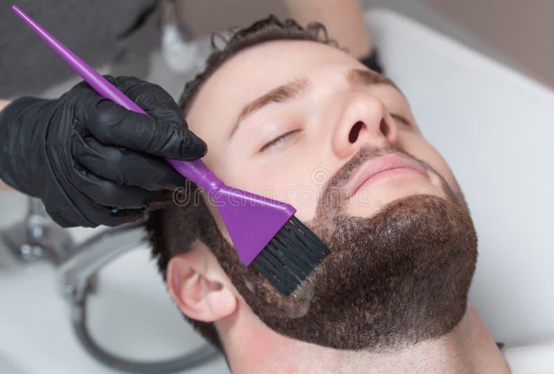 De kapper schildert de baard en de snor van de jonge man stock fotografie