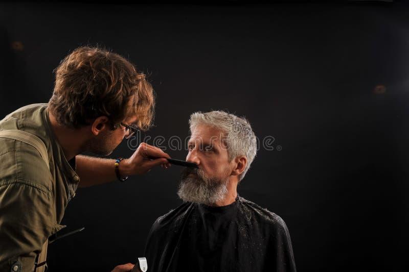 De kapper snijdt een baard aan een cliënt aan een bejaarde grijs-haired mens stock afbeelding