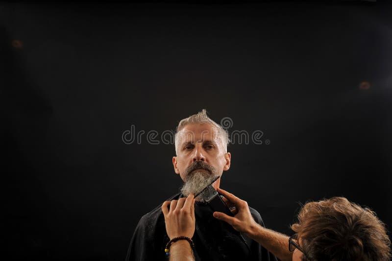 De kapper snijdt een baard aan een cliënt aan een bejaarde grijs-haired mens stock foto's