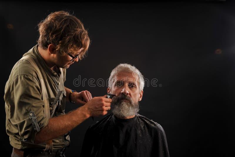 De kapper snijdt een baard aan een cliënt aan een bejaarde grijs-haired mens stock afbeeldingen