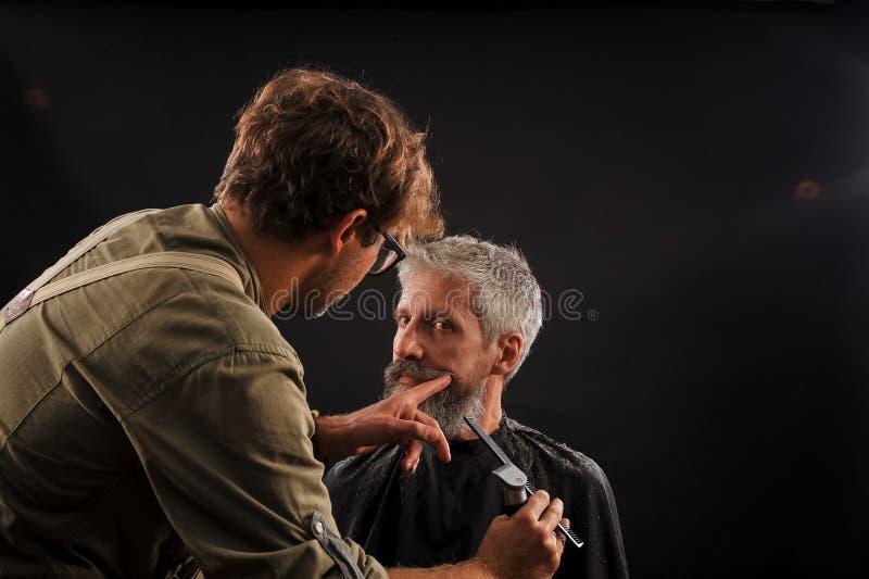 De kapper snijdt een baard aan een cliënt aan een bejaarde grijs-haired mens stock fotografie