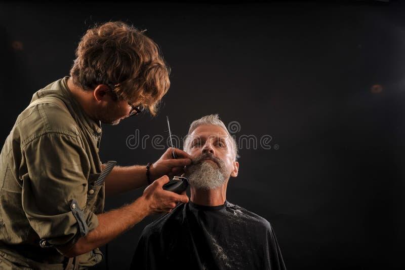 De kapper snijdt een baard aan een cliënt aan een bejaarde grijs-haired mens royalty-vrije stock foto