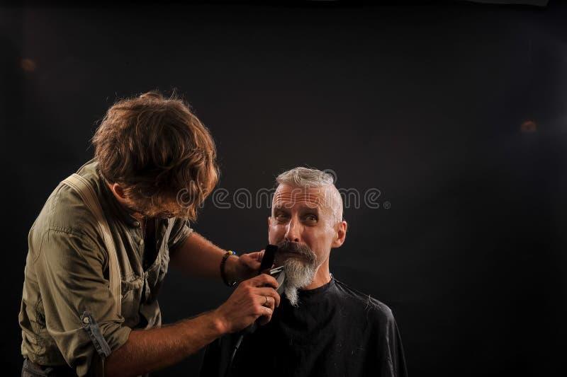 De kapper snijdt een baard aan een cliënt aan een bejaarde grijs-haired mens royalty-vrije stock afbeeldingen