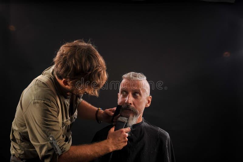 De kapper snijdt een baard aan een cliënt aan grijs-haired bejaarden royalty-vrije stock afbeelding