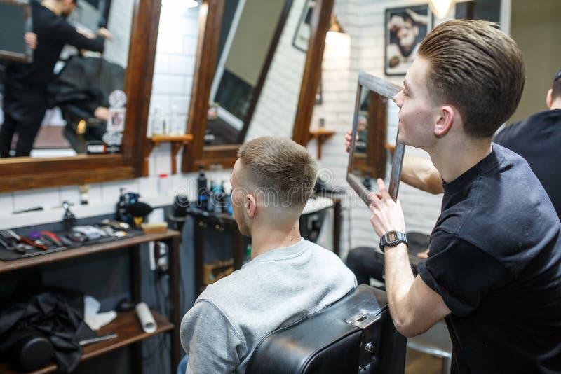 De kapper toont kort kapsel met spiegel aan knappe tevreden cliënt in professionele herenkapper royalty-vrije stock afbeeldingen