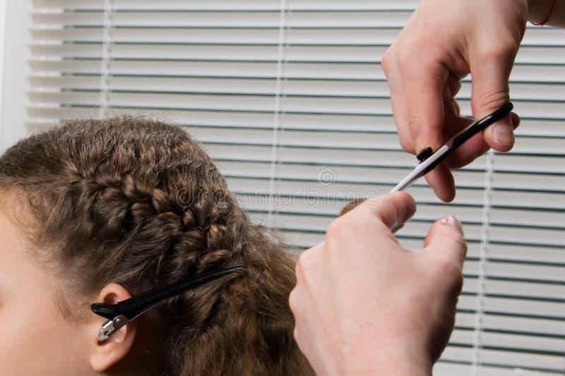 De kapper vlecht de vlecht aan het kind en snijdt de einden van het haar, met schaar stock afbeelding
