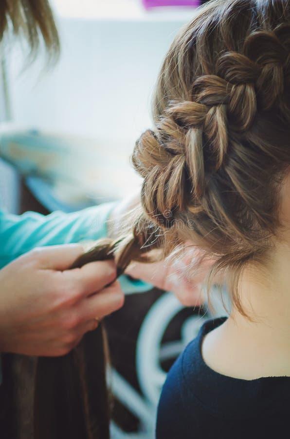 De kapper vlecht het vlechtmeisje Handen, close-up mooi kapsel Verticale Fotografie stock afbeelding
