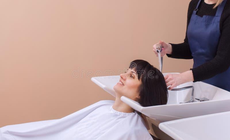 De kapper wast de shampoo van het haar aan een jong meisje, brunette royalty-vrije stock afbeeldingen