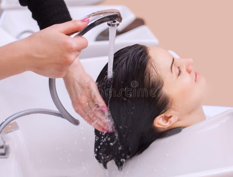 de kapper wast de shampoo van het haar aan een jong meisje, brunette stock foto's