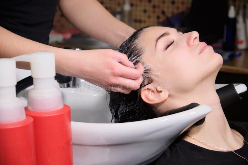 De kapper wast haar met shampoo aan donkerbruin meisje in een schoonheidssalon royalty-vrije stock afbeeldingen