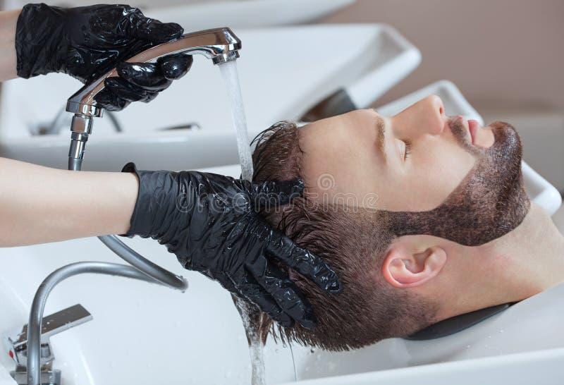 De kapper wast het hoofd van de jonge man met shampoo na kapsels royalty-vrije stock foto