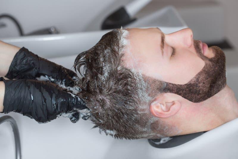 De kapper wast het hoofd van de jonge man met shampoo na kapsels royalty-vrije stock foto's