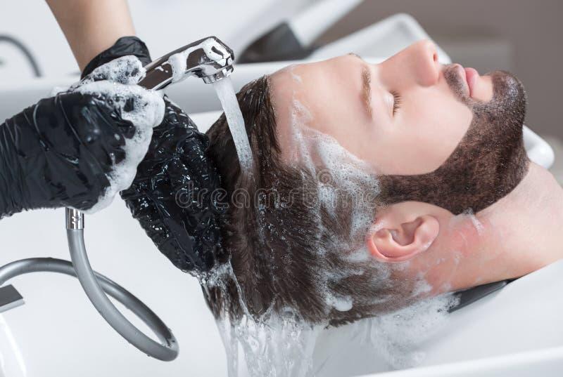 De kapper wast het hoofd van de jonge man met shampoo na kapsels stock afbeelding